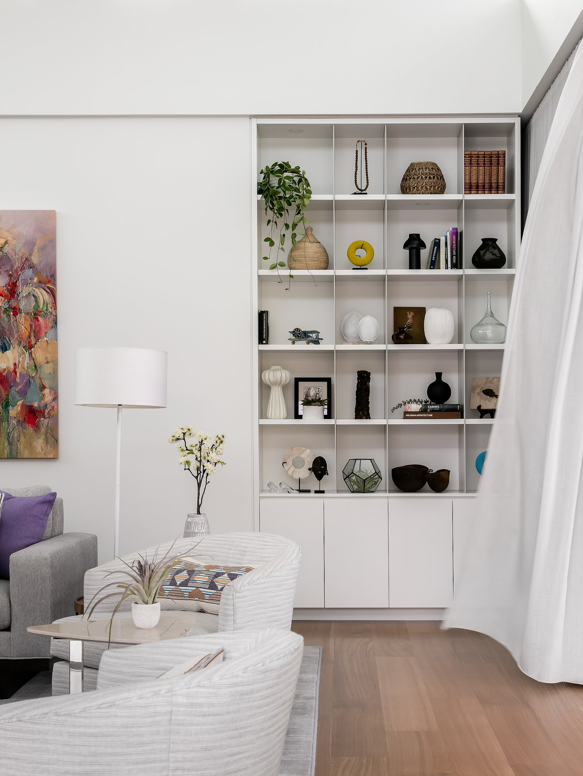 Living Room, Recessed Lighting, End Tables, Chair, Console Tables, Shelves, Medium Hardwood Floor, Storage, Ceiling Lighting, Lamps, Bookcase, and Accent Lighting  Bayview House by Leader Design Studio