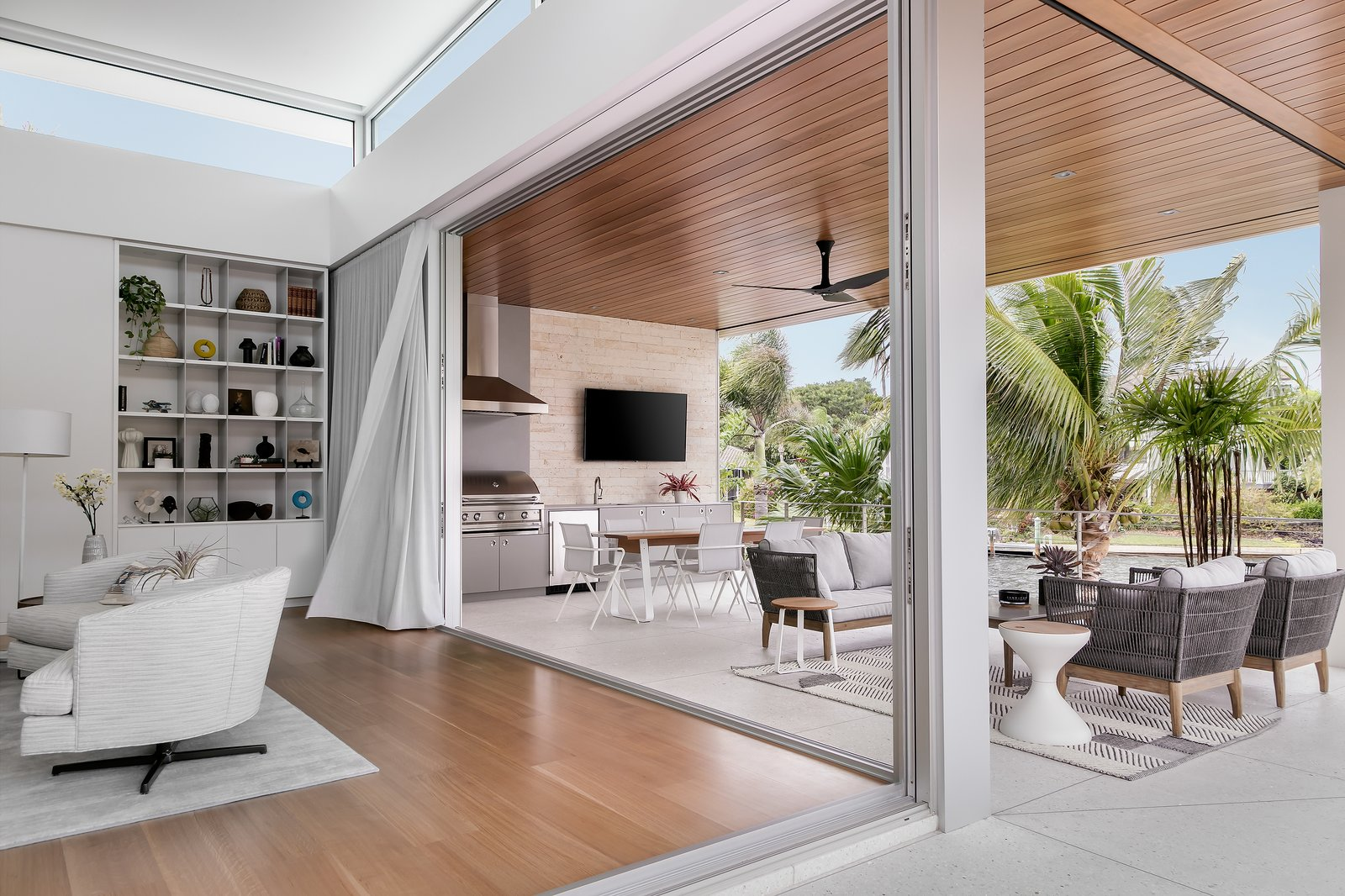 Living Room, Chair, Sectional, Coffee Tables, End Tables, Bookcase, Ceiling Lighting, Sofa, Floor Lighting, Recessed Lighting, Concrete Floor, Medium Hardwood Floor, and Accent Lighting  Bayview House by Leader Design Studio