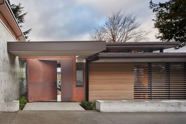A custom Cor-Ten steel pivot door leads into the lakefront home