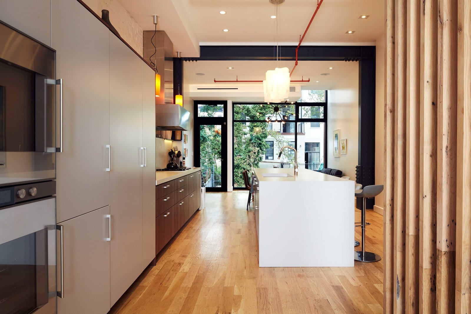 Kitchen, Engineered Quartz Counter, Refrigerator, Pendant Lighting, Medium Hardwood Floor, Cooktops, Wall Oven, Range Hood, and Undermount Sink  Harlem Townhouse by Opera Studio Architecture