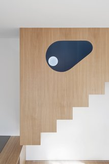 The eye-shaped hole of the stairs volume allows the spaces to stay connected.