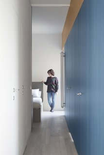 With the sliding mirrored door open, the corridor allows light from the bedroom to suffuse the entire space.