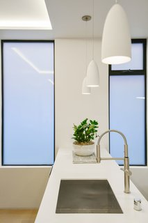 Tinted glass windows protect this white kitchen's luminous sheen.
