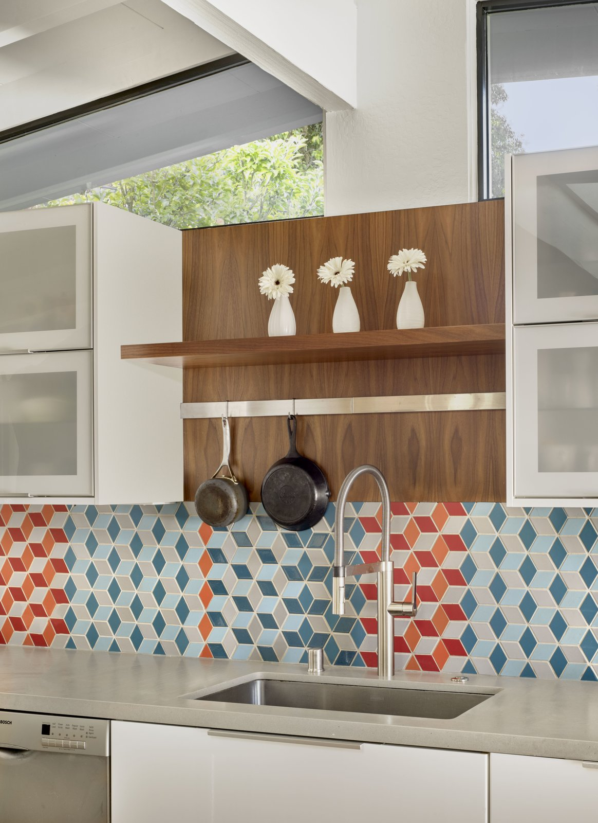 The kitchen features crisp, white cabinets, colorful mosaic tiles, and walnut accents.