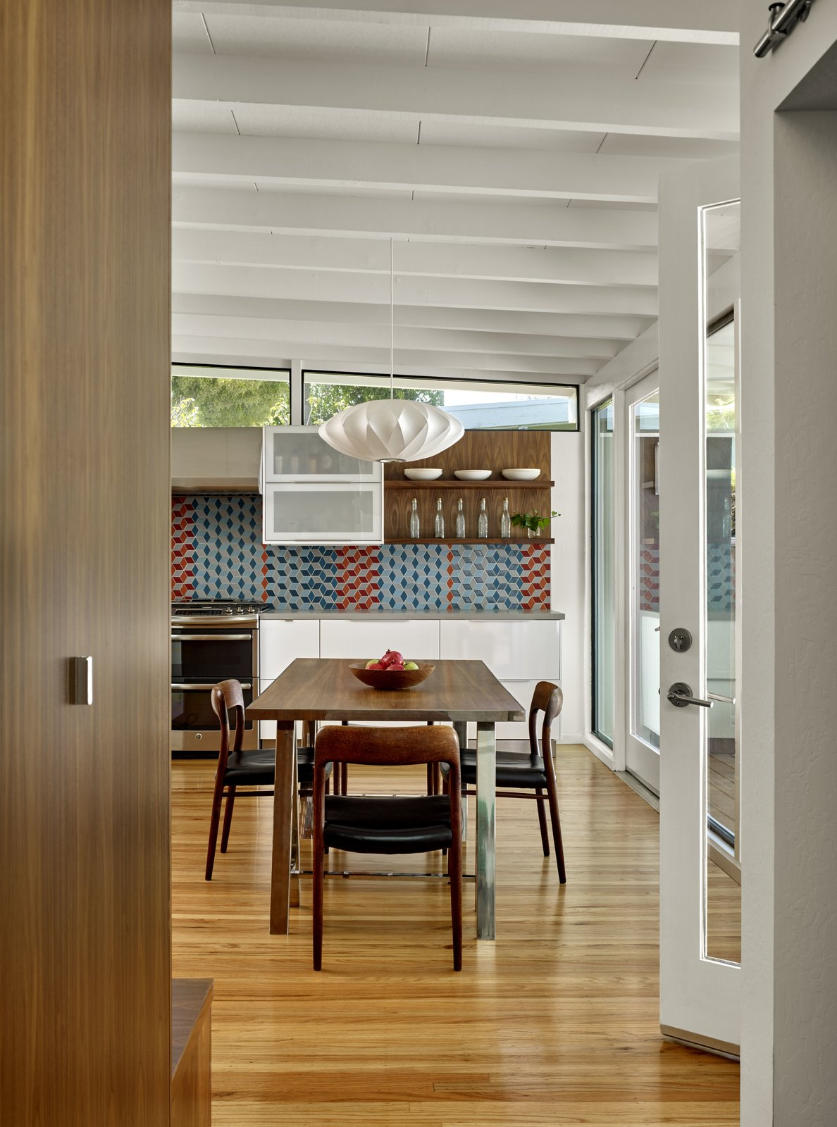 Custom walnut built-ins offer hidden storage along one side of the hallway.