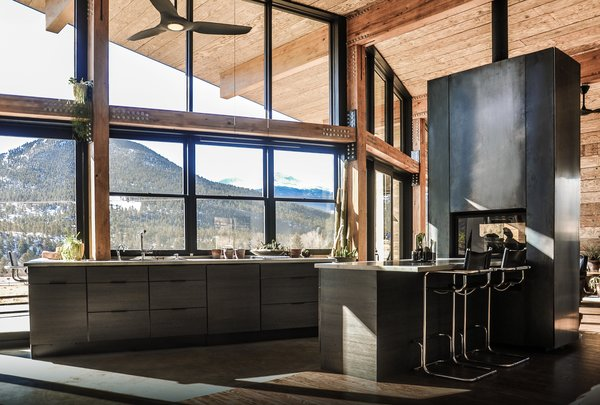 The warm industrial kitchen celebrates views of Rocky Mountain National Park beyond. A see-through, steel fireplace becomes a glowing beacon that warms the kitchen and living room at the heart of the home.