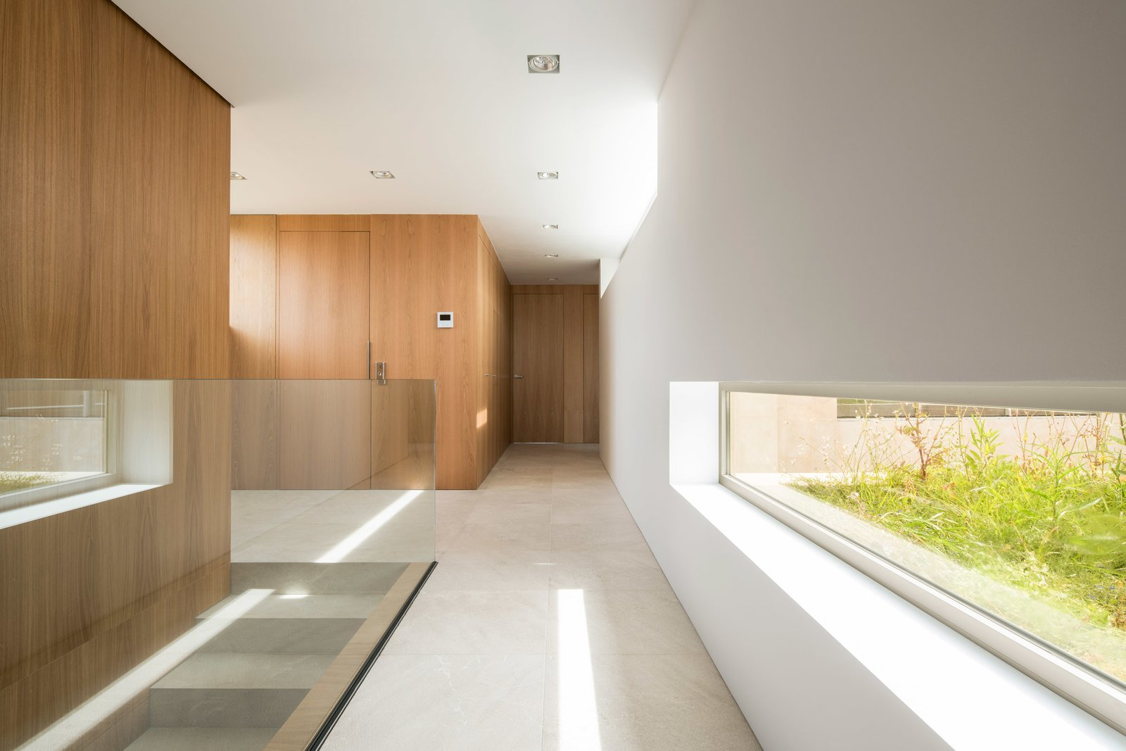 Hallway and Limestone Floor  M3 House by OLARQ Osvaldo Luppi Architects