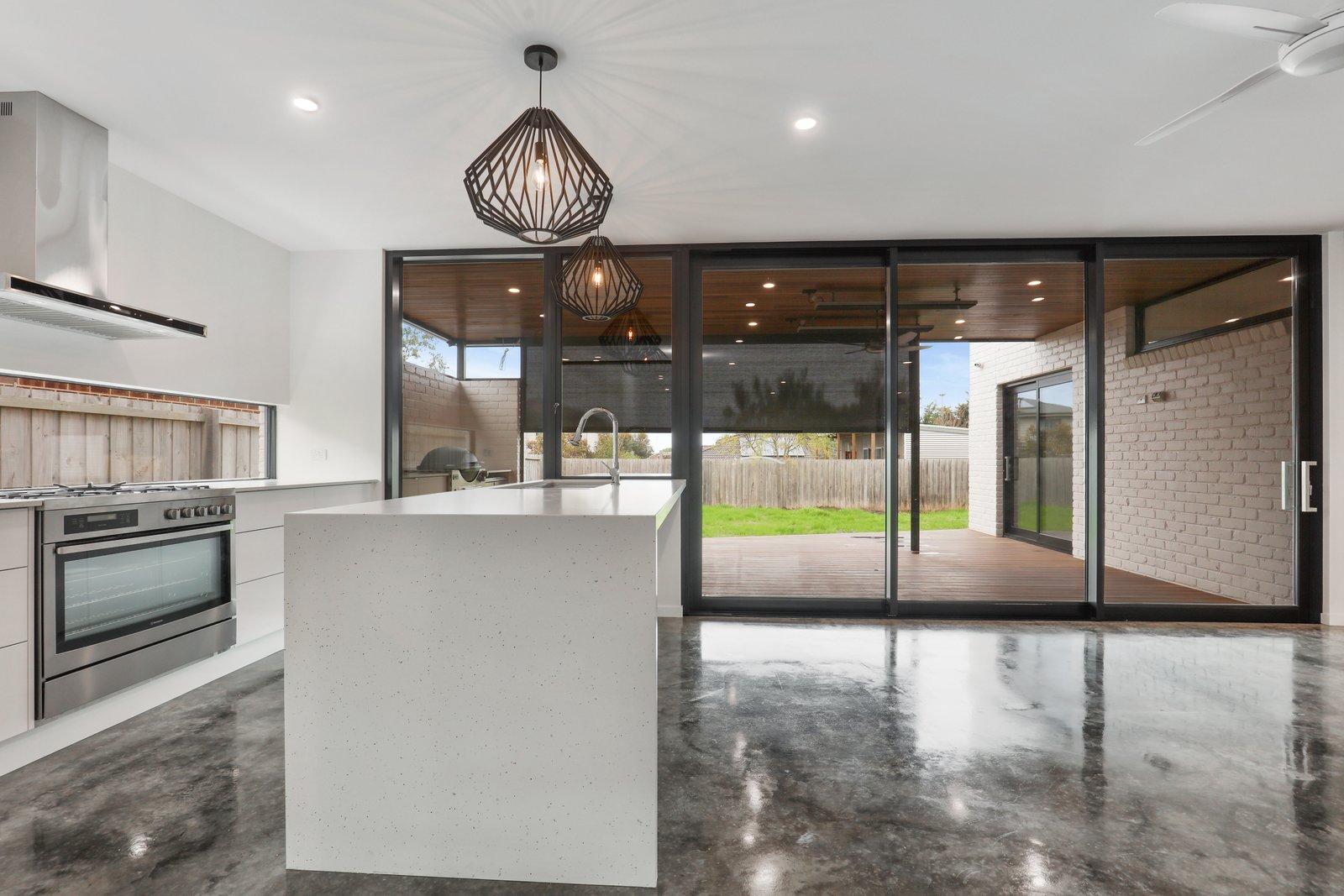 Kitchen, Engineered Quartz Counter, Glass Tile Backsplashe, Concrete Floor, Range, Pendant Lighting, White Cabinet, Recessed Lighting, and Undermount Sink  Tamara Crecsent by Inverloch 3996