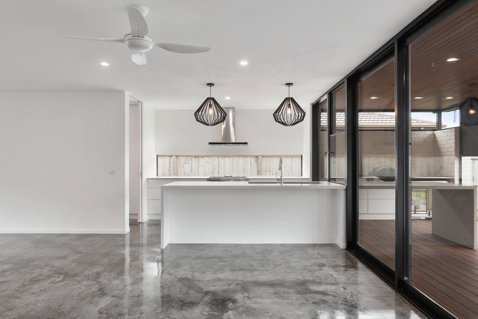 Wood Railing, Wood Tread, Dining Room, Concrete Floor, Pendant Lighting, and Recessed Lighting  Tamara Crecsent by Inverloch 3996