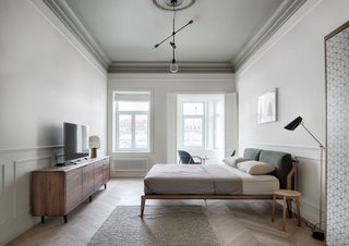 A large, exposed bulb hangs lower than its peers on a three-bulb pendant. The simple design effectively spreads subtle but diffuse light across this elegant, neutral-toned bedroom.