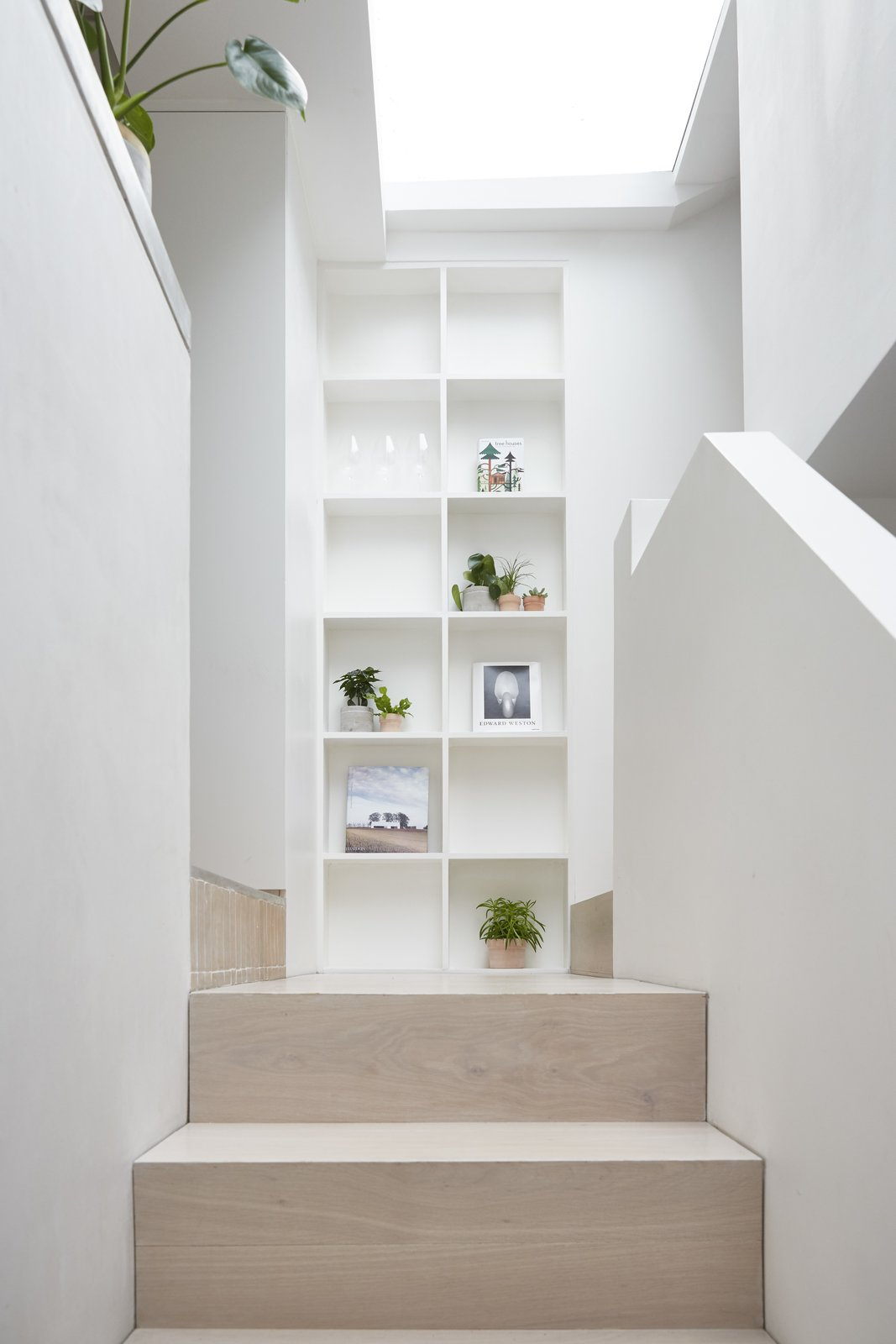 A new stair to the kitchen is clad in oak, and natural light floods in from the roof light above