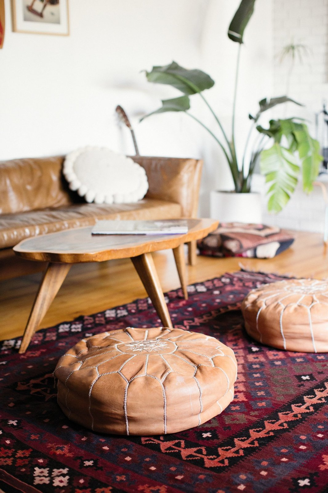 Living Room, Ottomans, Medium Hardwood Floor, Sofa, Rug Floor, and Coffee Tables There's also a global aesthetic to Julia's design choices.  Photo 11 of 15 in Too Cool: This Boho Surf Shack Has a Half-Pipe in the Backyard
