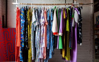 Dozens of examples of her brightly colored graphic prints are on display in some form — a rack of silky dresses, linen jumpsuits, and color-blocked jackets from her spring collection greet guests as soon as they walk in; a stack of dog beds, usually occupied by her Boston terrier, Snips, is in one corner, across from a pile of patterned and embroidered throw pillows; shelves are stacked with graphic bath and beach towels, fruit-printed bed linens and cozy blankets; poster boards of some of her most loved prints are both hung and leaning against any available wall space.
