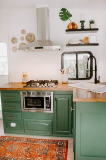 The biggest changes were made to the kitchen. Here, they removed all the cabinets in the upper section and added open shelving, a vent hood, a backsplash of white hexagon tiles, and lovely gold accents.