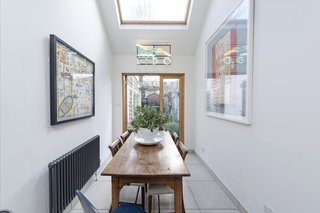 Glazed French doors, elevated ceilings, and a large skylight allow the light to flow through and illuminate the dining area.
