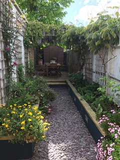The 45-foot garden is low maintenance and has a feeling of seclusion and privacy,  with a dining area enclosed by a pergola overhung with wisteria.