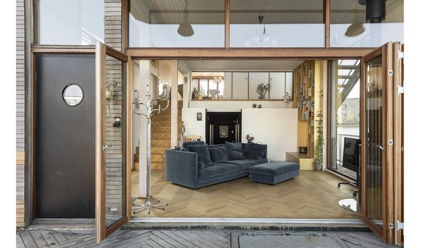 The living room's bi-fold doors offer unbroken views of the water.