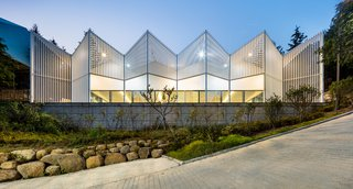 The community facility is formed of geometric shapes featuring white louvres made from steel.