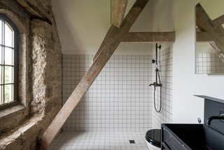 Monochrome, industrial, and minimalist, the utilitarian look of the bathroom fittings accentuate the building's rustic architectural features.