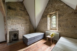 With its vaulted ceiling, tall narrow window, and exposed stone walls, this bedroom has the feeling of a convent or church building.