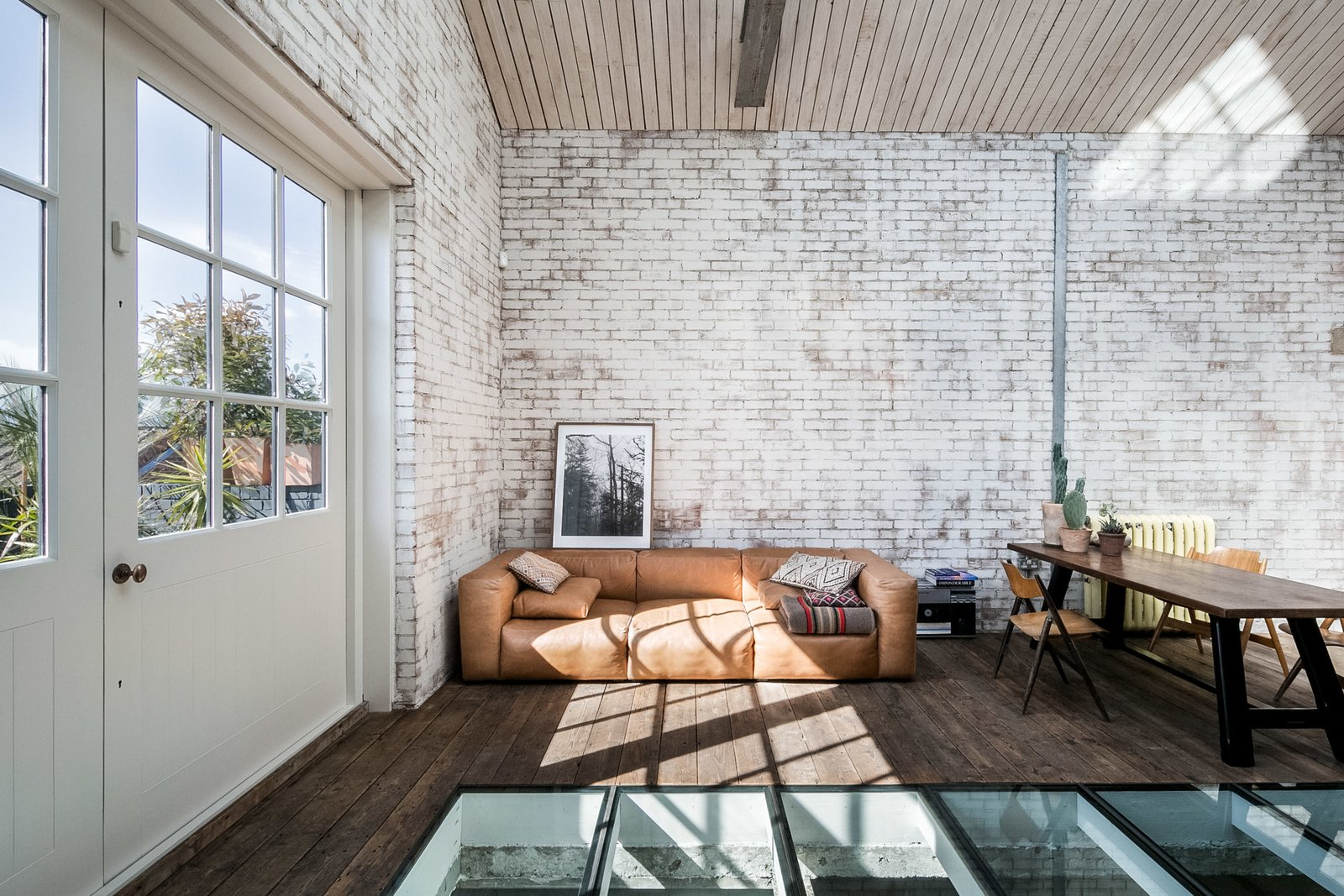 Dining Room, Chair, Table, and Dark Hardwood Floor A low-slung, tan leather sofa and the informal, bench-style table with vintage folding chairs work with the relaxed ambiance of the space.  Photo 5 of 11 in Snap Up This Converted  Warehouse in London For $2.1M