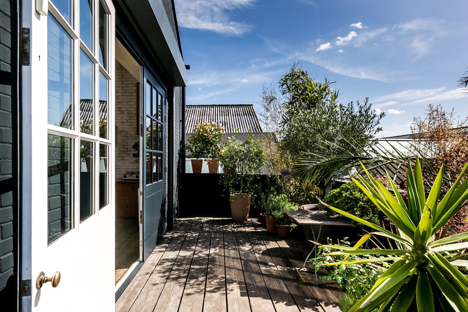 Doors, Exterior, Wood, and Sliding Door Type Painted in the same warm navy as the exterior walls, the two solid-wood living room doors create a seamless link between the living room and terrace.  Photo 7 of 11 in Snap Up This Converted  Warehouse in London For $2.1M