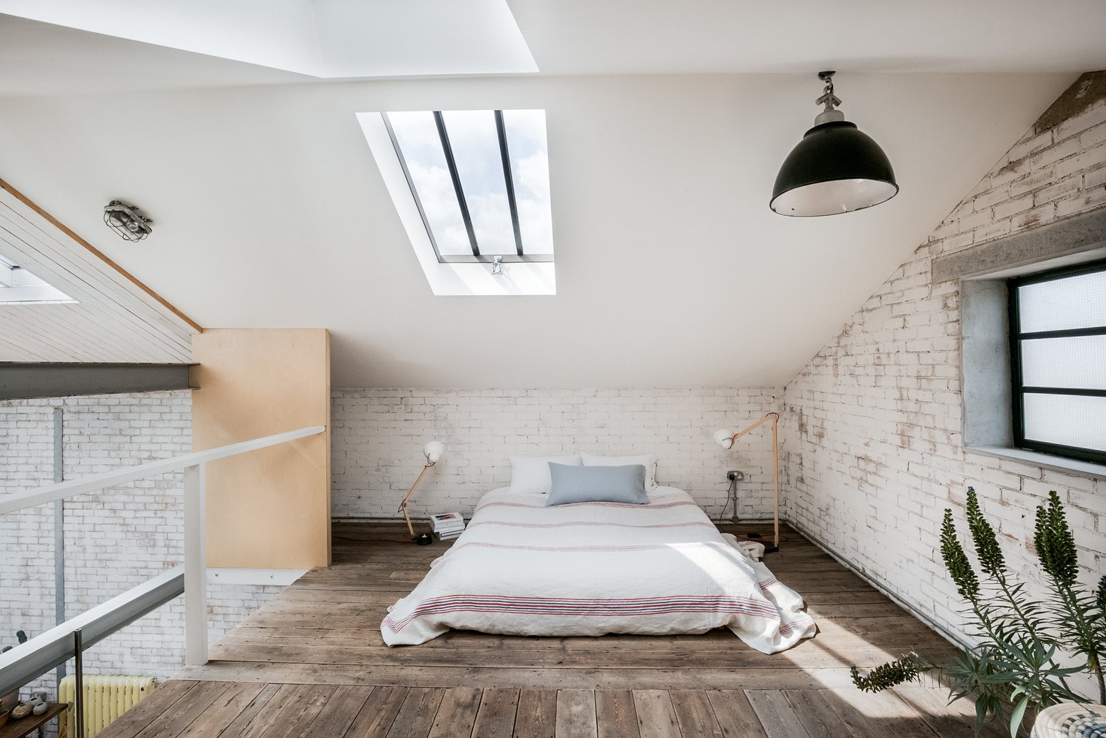 Bedroom, Pendant Lighting, Dark Hardwood Floor, Bed, and Table Lighting The floor-level bed makes best use of the space in the mezzanine-level bedroom. Luxury additions include recessed Crittall windows and two large skylights, which bring light streaming into the space.  Photo 3 of 11 in Snap Up This Converted  Warehouse in London For $2.1M