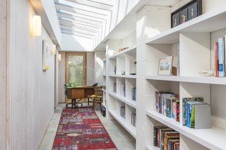 With a slanted glazed ceiling, a white fitted bookcase, and wood-clad walls,  the study is a light, bright space to work in, and has views of the garden thanks to the expansive glass doors.