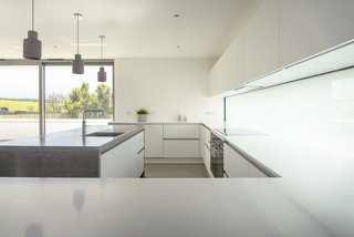 The abundance of white and gray surfaces and uninterrupted lines gives the kitchen a serene feel, which is enhanced by the views of the unspoiled countryside through the glazed doors. There is no shortage of worktop space, thanks to its C-shape design and large central island.