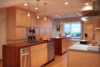 Modern home with Kitchen, Pendant Lighting, Range Hood, Wood Cabinet, Dishwasher, Light Hardwood Floor, Wood Counter, Wall Oven, Recessed Lighting, Stone Counter, and Undermount Sink. Photo  of Modern Remodel in Traditional Home