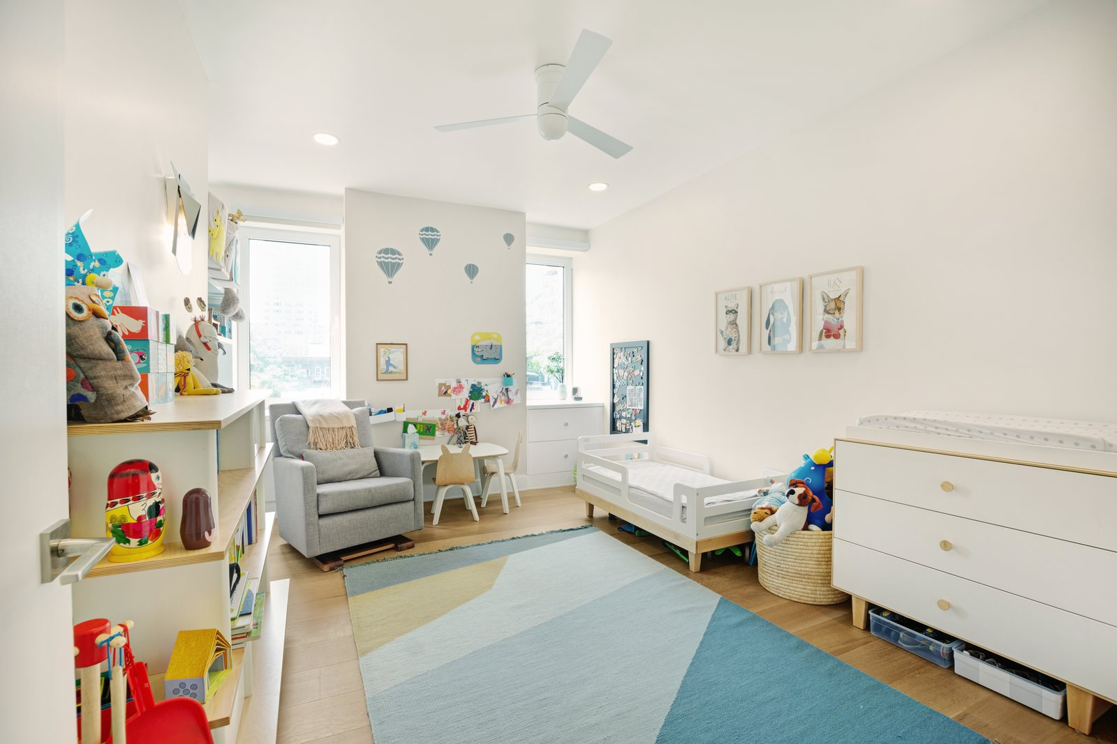 Kids Room, Medium Hardwood Floor, Toddler Age, Neutral Gender, Dresser, Bed, Bedroom Room Type, Rug Floor, Desk, Shelves, and Chair  Photos from Greenwich Village Renovation