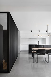 """""""Reinforcing the degree of abstraction of the project, the choice of the minimalist furniture and lamps echoes the palette of textures composed of concrete, wood, and steel,"""" add the architects."""