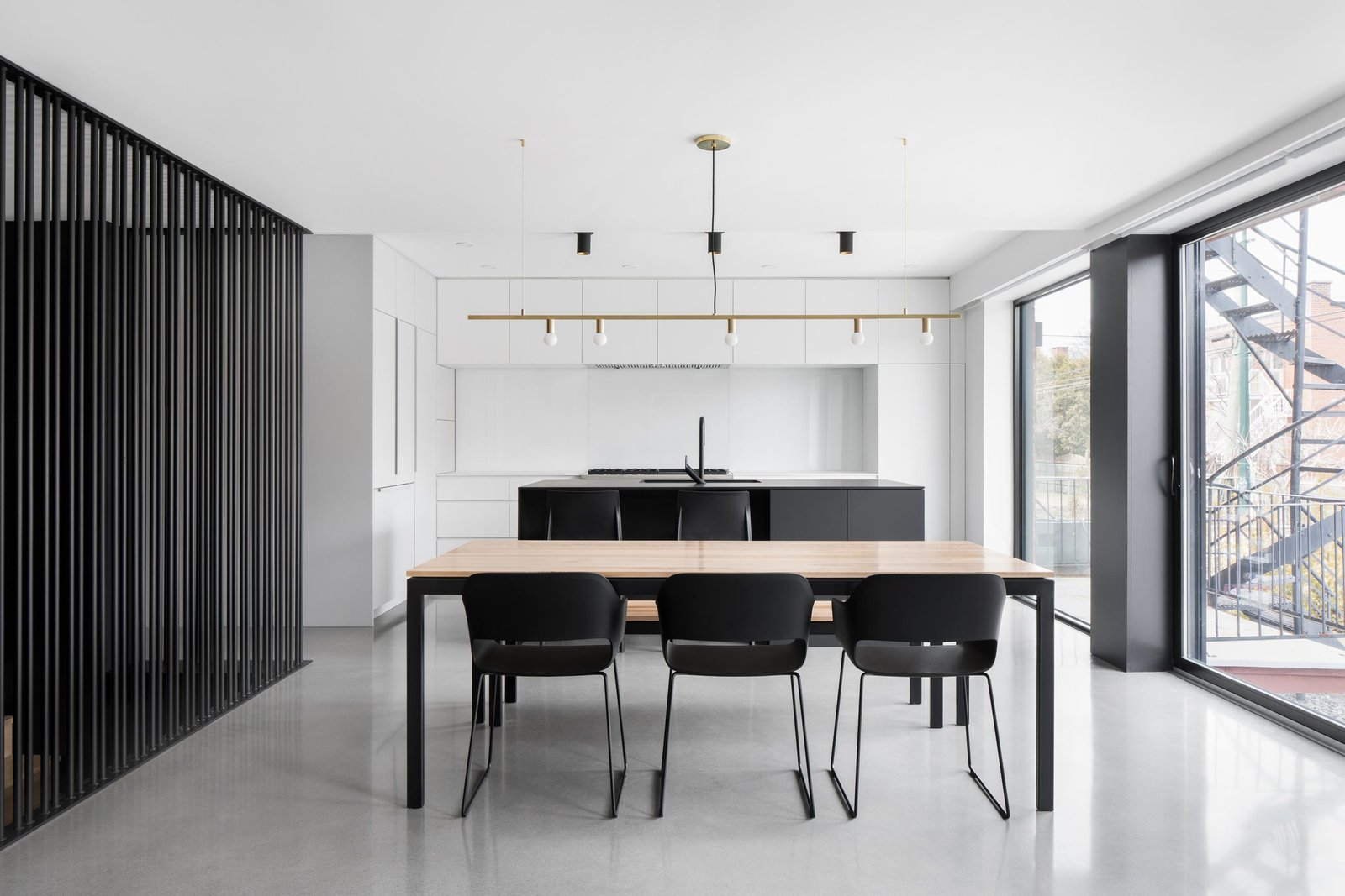 The kitchen bookends an open-plan layout that also includes a dining area and living room. Full-height windows help create a sense of spaciousness and open the living areas to the backyard.