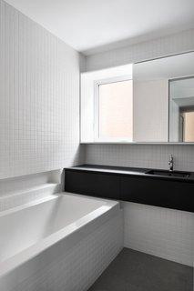 White square ceramic tiles cover the bathroom walls. The counters are Fenix Laminate (Arpa).