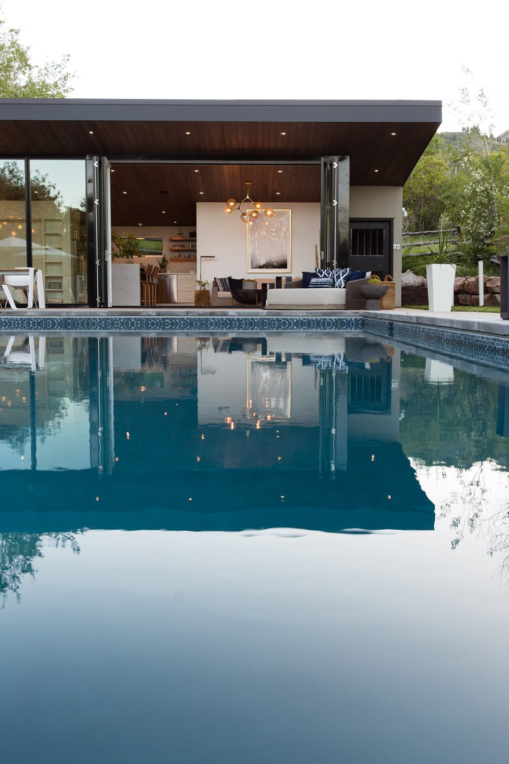 Outdoor, Back Yard, Concrete Patio, Porch, Deck, Shower Pools, Tubs, Shower, Swimming Pools, Tubs, Shower, and Concrete Pools, Tubs, Shower  Photo 7 of 16 in This Can-Do Pool House Cleverly Goes From Private to Party Mode from Modern Mountain Pool House