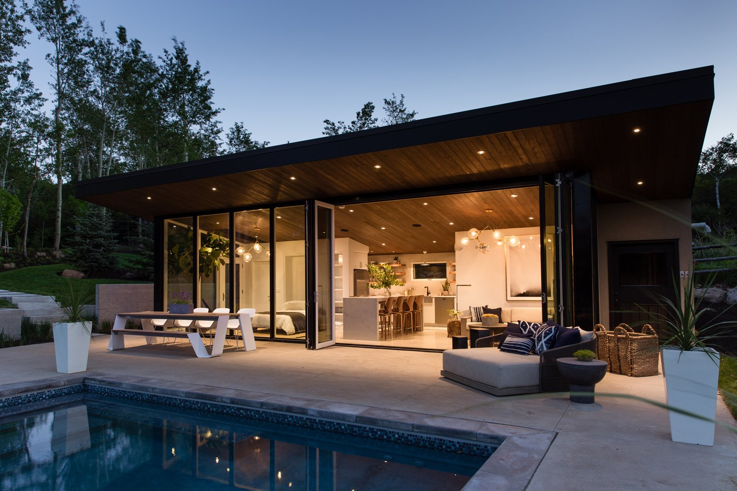 Exterior, Stucco Siding Material, Small Home Building Type, Metal Siding Material, Tiny Home Building Type, Metal Roof Material, Glass Siding Material, and Shed RoofLine  Photo 16 of 16 in This Can-Do Pool House Cleverly Goes From Private to Party Mode from Modern Mountain Pool House