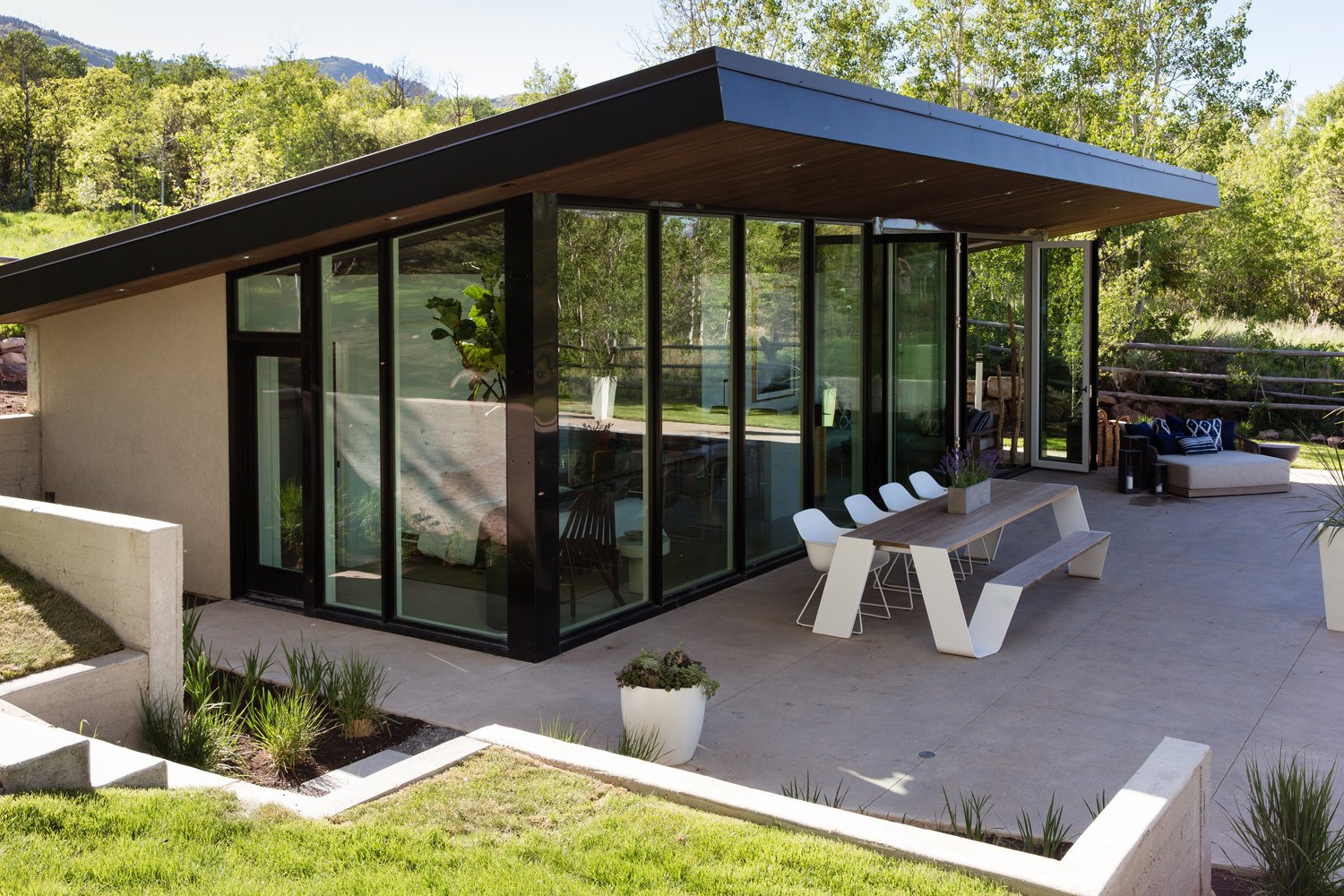 Exterior, Metal Roof Material, Glass Siding Material, Stucco Siding Material, Metal Siding Material, and Shed RoofLine  Photo 15 of 16 in This Can-Do Pool House Cleverly Goes From Private to Party Mode from Modern Mountain Pool House