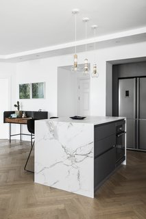 This apartment, overlooking the beautiful beach and the urban views of Tel Aviv, was built in the late 1990s and hadn't been renovated since, until designer Maya Sheinberger came in. The kitchen cabinets were chosen in a grey color with a matte finish and for the countertops, the designer chose a bright Dekton with marble texture. Above the kitchen island, which is used for cooking and for light family meals, are three wooden lighting fixtures by Israeli designer Ohad Benit.