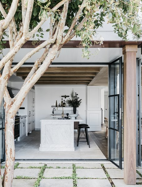 The kitchen now opens out to a courtyard and outdoor dining area thanks to large glass doors.