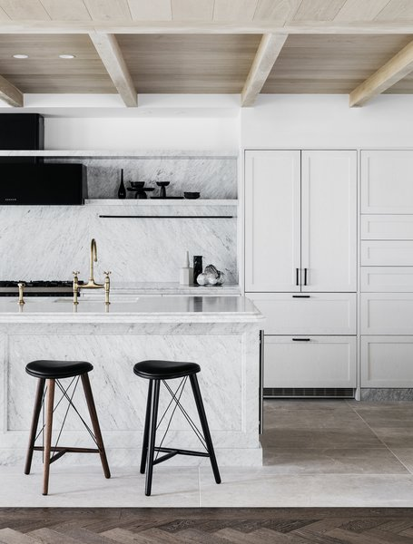 A marble island and white cabinetry define the bright, open kitchen, while matte black and bronze finishes celebrate craftsmanship.