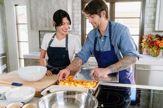 Ludo Lefebvre shows Athena Calderone how to load up veggies for steaming in a tray that will go into the Fisher & Paykel Built-In Combination Steam Oven.