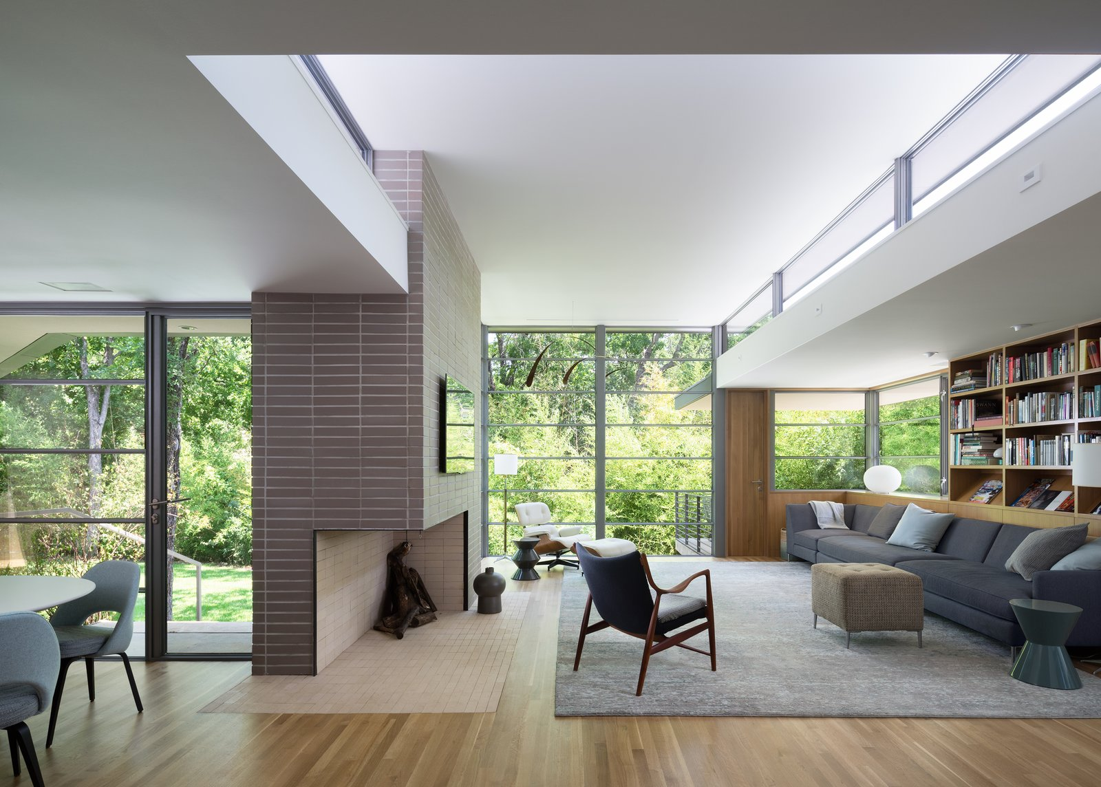 Living Room, Ottomans, Light Hardwood Floor, Bookcase, Chair, Corner Fireplace, End Tables, Recessed Lighting, and Sectional  Inwood Place by Tim Cuppett Architects