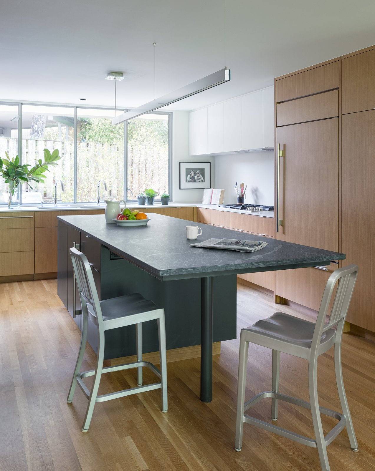 Kitchen, Stone Counter, Refrigerator, Wood Cabinet, Cooktops, Pendant Lighting, Light Hardwood Floor, White Cabinet, and Undermount Sink  Inwood Place by Tim Cuppett Architects