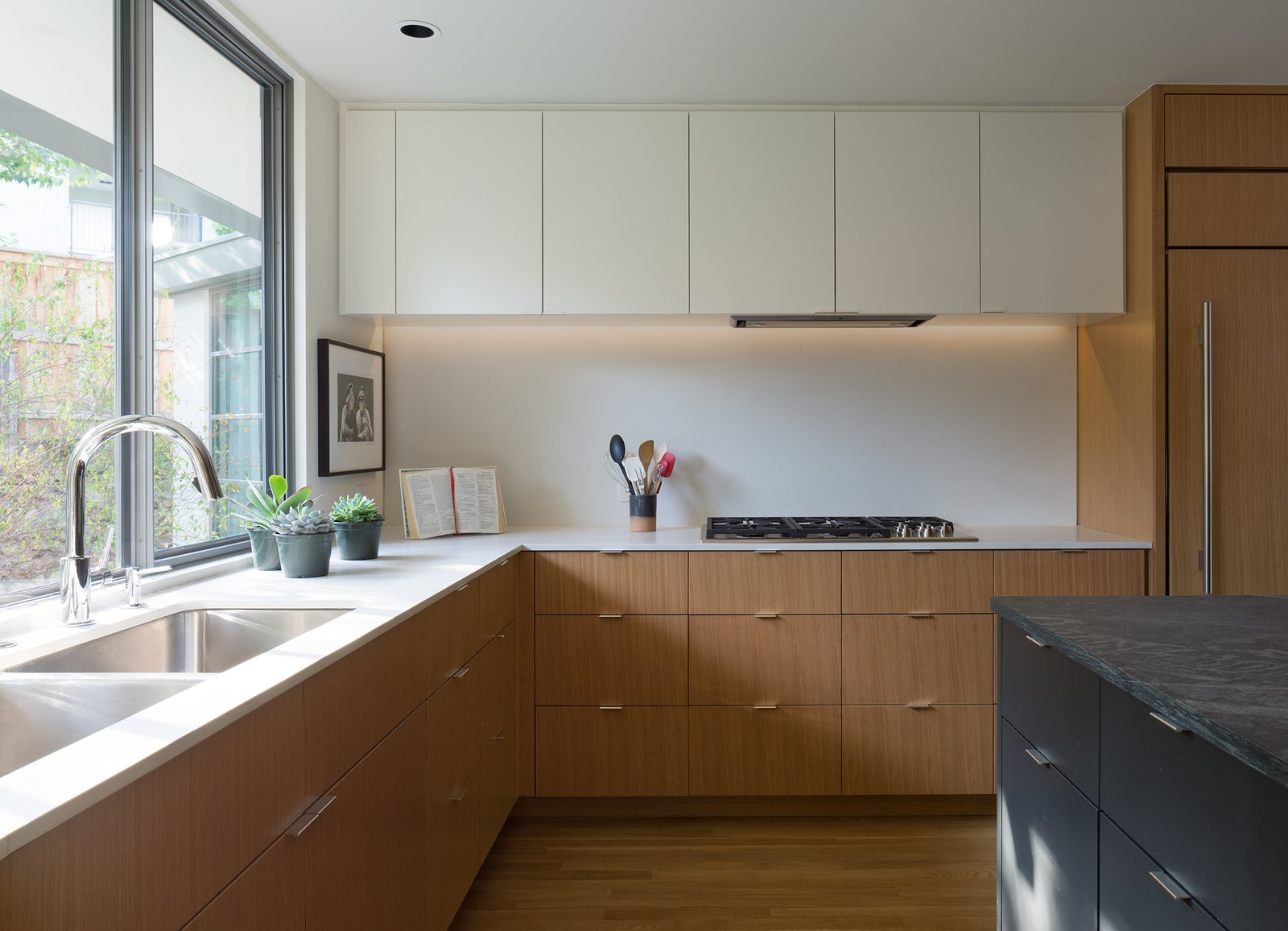 Kitchen, Concrete Counter, Light Hardwood Floor, Undermount Sink, Cooktops, Recessed Lighting, Stone Counter, and Refrigerator  Inwood Place by Tim Cuppett Architects