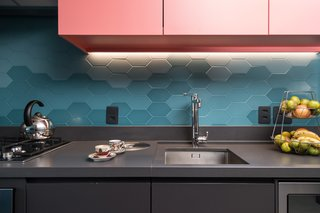 Three tropical shades of blue make for a bold backsplash in this kitchen in Brazil. The elongated hexagonal shape of the tiles is a new take on a classic tile shape, and pairs with the dark cabinetry and countertops.
