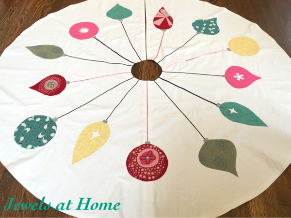 Add a touch of whimsy to your Christmas tree with this adorable tree skirt. Embroidered with colorfully patterned ornaments that pop against a white background, it's one of our favorite midcentury modern Christmas decorations.