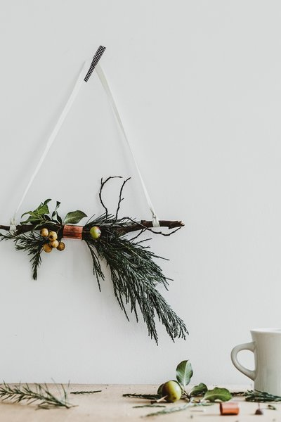 This simple, chic modern holiday decor makes for an easy DIY project. Gather your favorite greenery and a sturdy twig, and bind them together with a copper band for a metallic accent—or your favorite ribbon. For a more classic Christmas vibe, add a poinsettia into the mix.