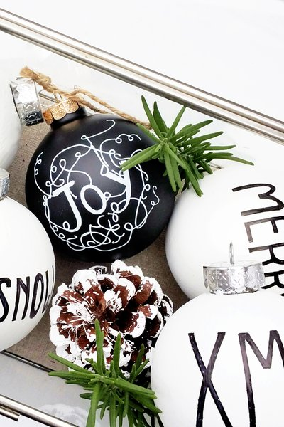If you're looking to DIY your modern Christmas decor this year, look no further than these simple black and white orbs inscribed with holiday-inspired messages. All you need to create this look is the ornaments, a white paint pen, and a black Sharpie. These modern Christmas ornaments are a great way to stay on budget and on trend.