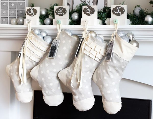 Simple details and a neutral color palette characterize these modern Christmas stockings that depart from the traditional red-and-white scheme. They're right at home and ready to be filled as they hang from the mantle by monogrammed stocking holders adorned with vintage knobs.