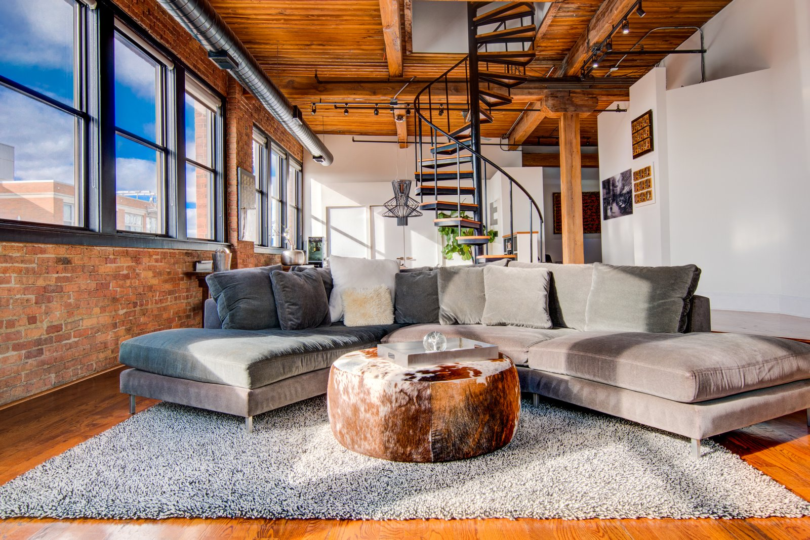 Living Room, Ottomans, Medium Hardwood Floor, Sectional, and Track Lighting  Penthouse That Starred on NBC's 'Chicago Fire' Asks $1.775M